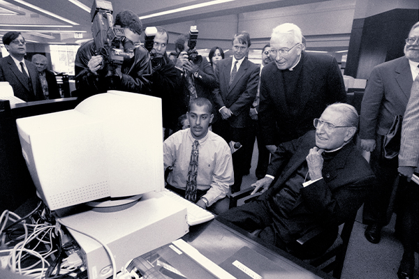 In 1997, John Cardinal O'Connor (right) blessed the William D. Walsh Family Library, then joined Father O'Hare and Mohammad Kahn (FCO '00) for a tour of the Vatican's website.