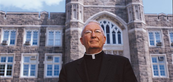 Father Joseph A. O'Hare, S.J. in front of Keating Hall.