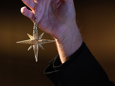 A hand holding up a gold star ornament