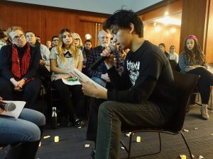 A young man wearing a black shirt sits and reads from a piece of paper.