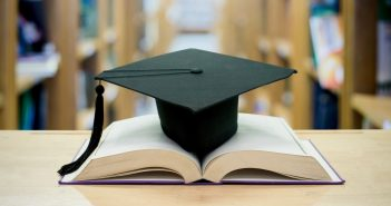 A black graduation cap on an open book