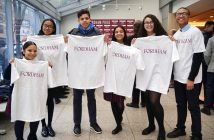 Students holding white Fordham t-shirts