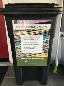 "A black of books with the sticker ""BOOK DONATION BIN"""