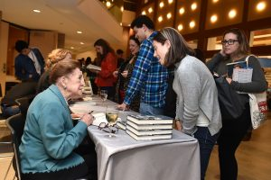 Mary Higgins Clark speaking to a student while seated at a table.