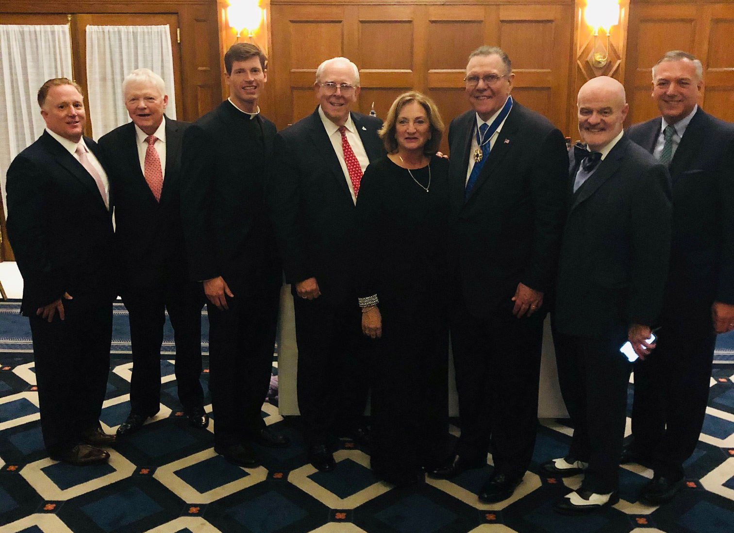 group photo of Fordham alumni attending a reception following the awarding of the Medal of Freedom to retired General Jack Keane