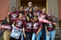 A group of teenagers wearing Fordham gear on the steps of Cristo Rey New York High School