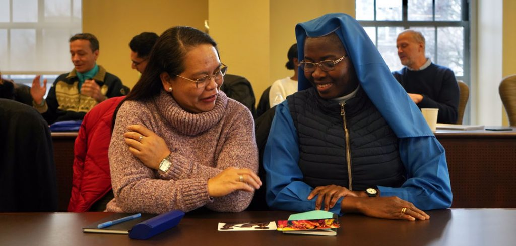Two women sit beside each other and smile at cards on a table before them.