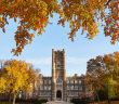 A big, Gothic-style building surrounded by orange autumn branches