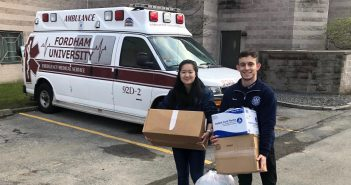 Two students hold boxes in front of an ambulance.