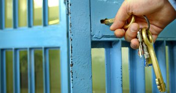 stock art of hand insterting key into jail cell