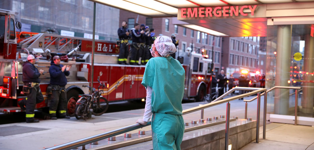 Fordham graduate and registered nurse Kyle Mitchell looks at firefighters in a Manhattan street saluting health care workers responding to the coronavirus pandemic