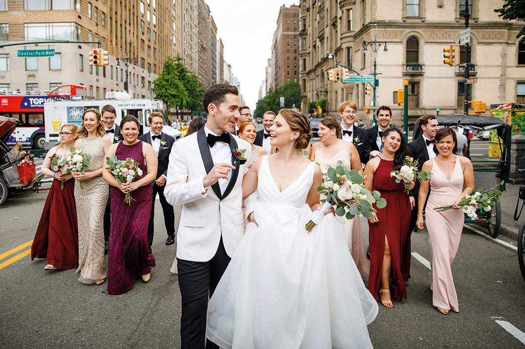 Fordham alumni Tim Dinneen and Sarah Dreher, dressed in white tuxedo and wedding gown, walk through Manhattan on their wedding day, August 16, 2019, with their wedding party behind them