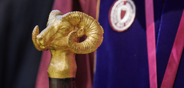 A golden ram head statue on a stick