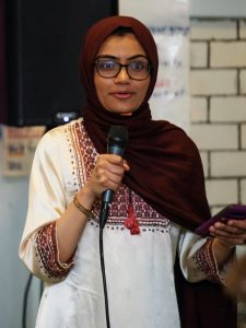 A woman wearing a hijab and glasses speaks into a microphone.