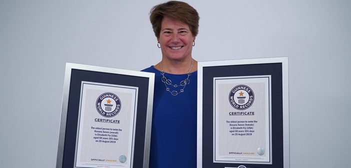A woman holds two awards