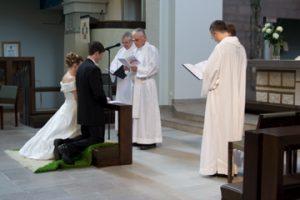 A bride and groom kneeling before men wearing white