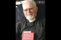 An elderly man wearing a black priest robe and holding a red book