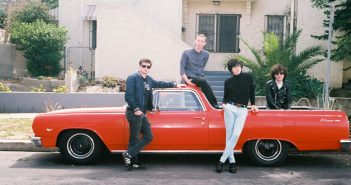 A promo photo of Car Seat Headrest posing on a red car.