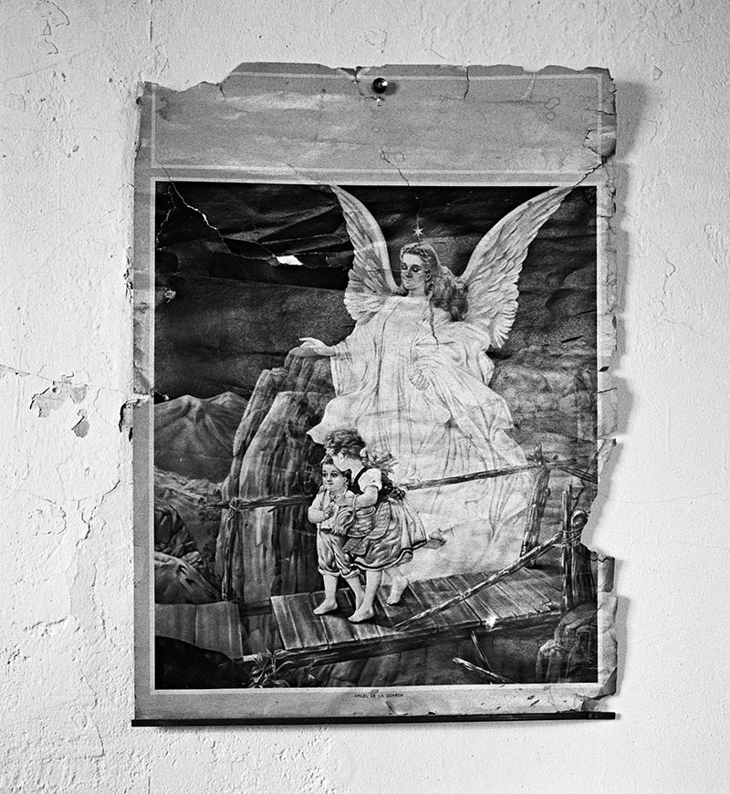 This black-and-white photo shows the top half of a wall calendar featuring an image of a guardian angel and two children crossing a bridge.