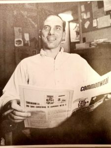 A sepia photo of a man smiling and holding a newspaper