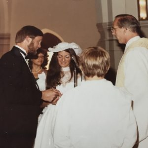 A groom, bride, and other people standing in a circle