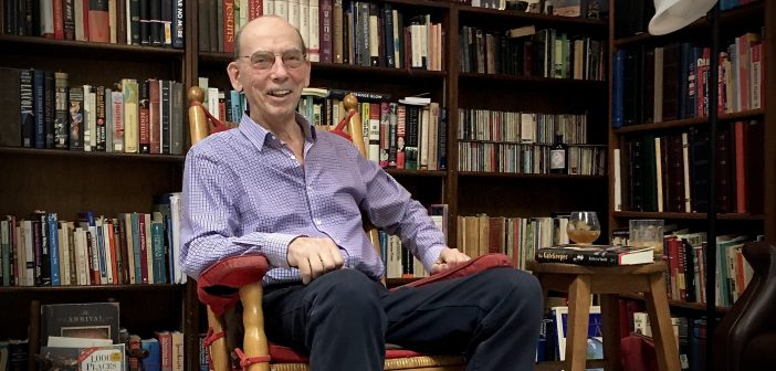 A smiling elderly man sitting in front of a row of bookshelves