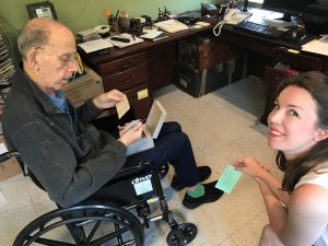 A man sitting in a wheelchair, holding a box of index cards, and a smiling woman beside him