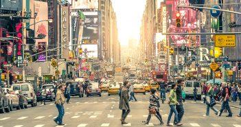 People walk across a street in New York City