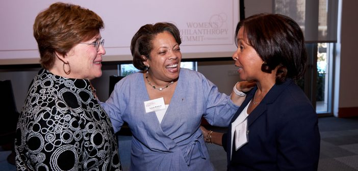 Three women stand next to each other and laugh.