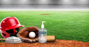 A baseball helmet, glove, and hand sanitizer on a field