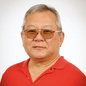 A portrait of a smiling man wearing tinted eyeglasses and a red shirt