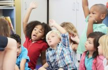 Children sit on a classroom carpet and excitedly raise their hands.