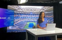 A woman wearing a blue dress smiles in front of a screen picturing an empty tennis court.