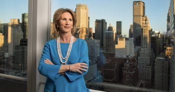 A woman wearing a blue shirt and long necklace stands in a building in front of the Manhattan skyline.