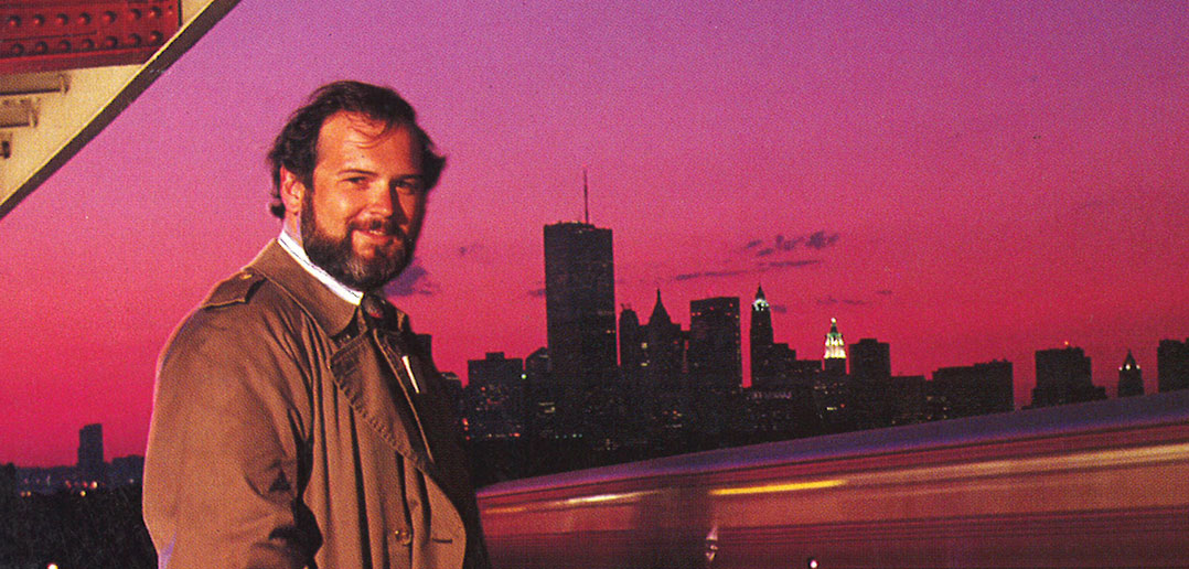 Fordham graduate Jim Dwyer stands on an elevated subway platform with the downtown Manhattan skyline in the background, 1991