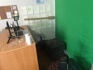 a desk with a green screen behind it.