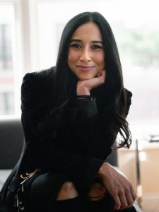 A woman wearing all black smiles at the camera with her chin propped under her hand.