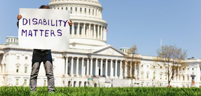 "A boy stands in front of the Capitol Building and holds a handmade sign that says ""DISABILITY MATTERS."""