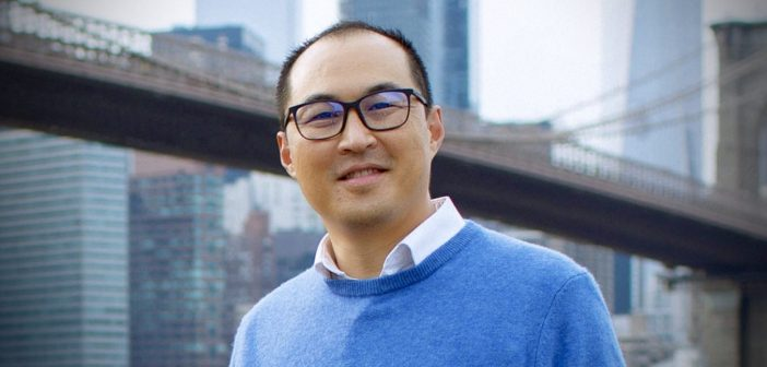 A man wearing black glasses and a blue sweater smiles in front of a bridge.