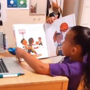 A little girl holds a book in front of an open laptop.