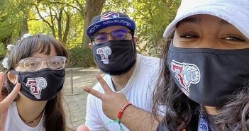 Three students smiling in a selfie while wearing black masks that have a ram and a giant F