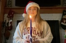 A young woman wearing a red Santa hat holds a taper candle and smiles at the camera.