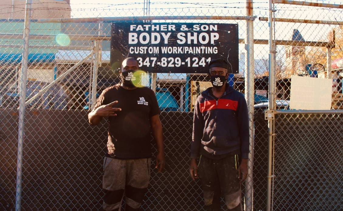 "Two men wearing masks stand in front of a sign that says ""FATHER & SON BODY SHOP."""