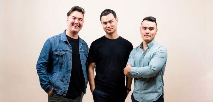 Three men pose next to each other.