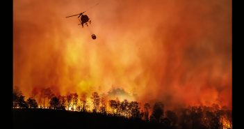 A helicopter flying above a burning landscape