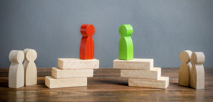 A red block figurine and a green block figurine on top of a pile of wooden blocks
