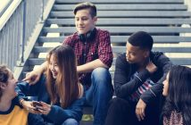 Five teenagers sit on a stairwell and chat.