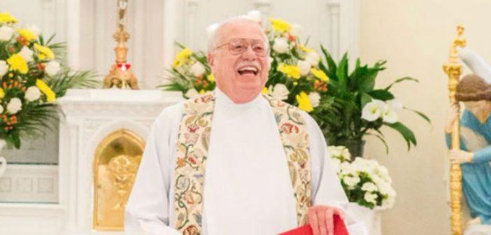 Father John Denniston standing at an altar