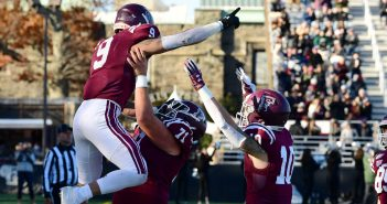 A football player jumps into the air, surrounded by teammates