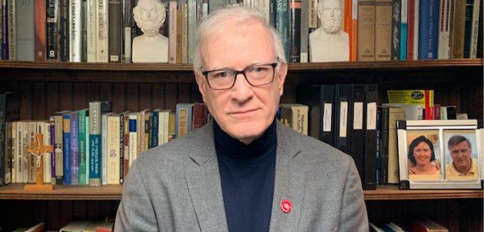Tom Hughes, GSAS '79, poses in front of a bookshelf.